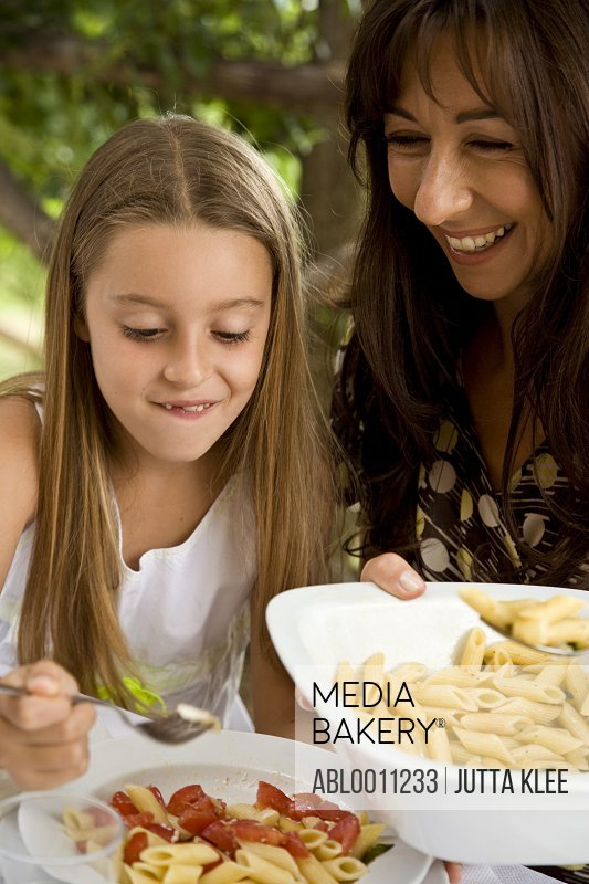 Mother serving pasta to daughter