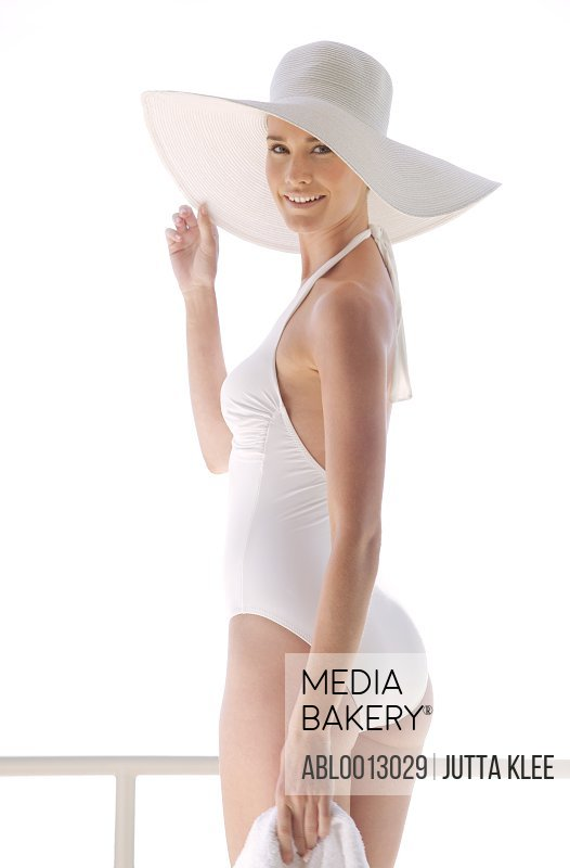 Portrait of a woman in white swimsuit holding the brim of her hat