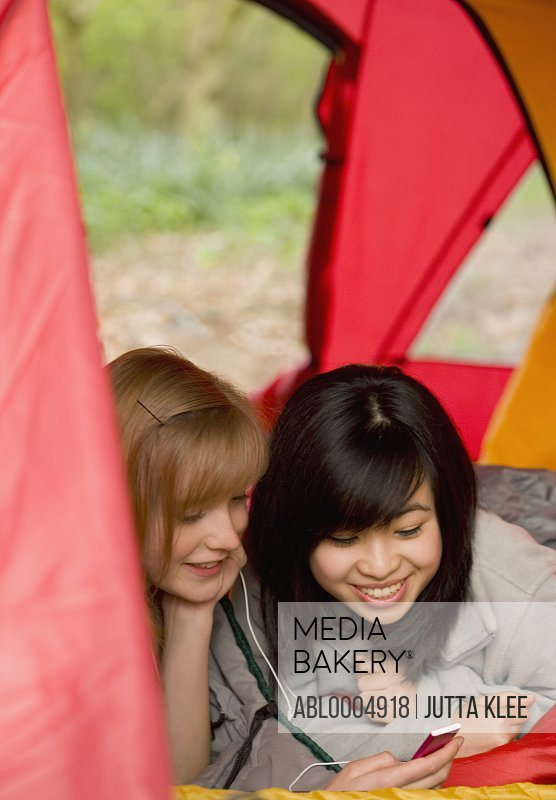 Two smiling teenaged girls lying in a tent holding a mp3 player listening to music