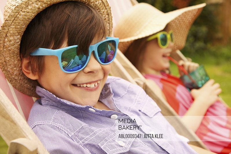 Boy and Girl Wearing Straw Hat and Sunglasses Smiling