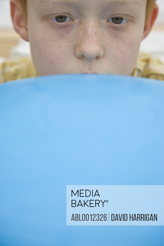 Close up of a boy face partly covered by a blue exercise ball