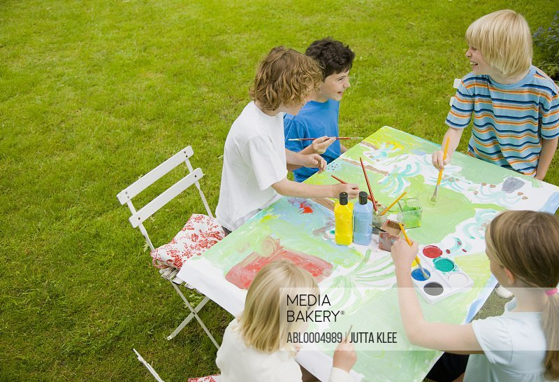 Children sitting and painting in the garden