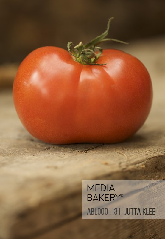Close up of a red vine tomato on a wooden surface