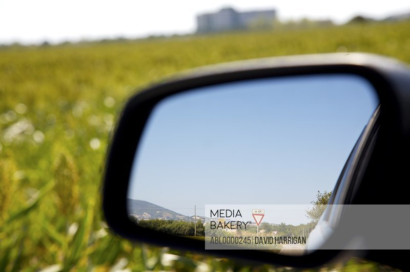 Close up of side view mirror reflecting blue sky and road sign