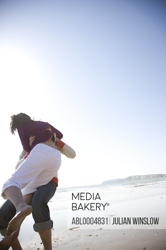 Young couple  playing and messing around on a beach - man lifting woman