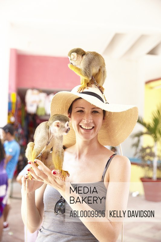 Woman Posing with two Spider Monkeys one Sitting On top of her Head