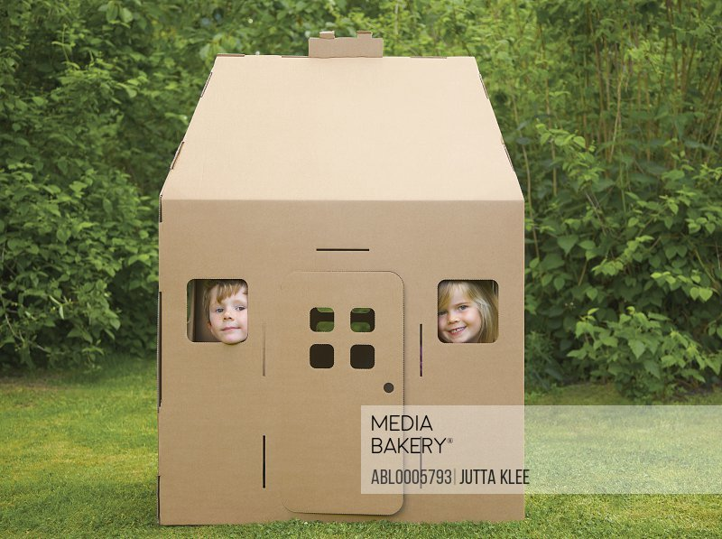 Boy and girl looking out from the windows of a cardboard playhouse