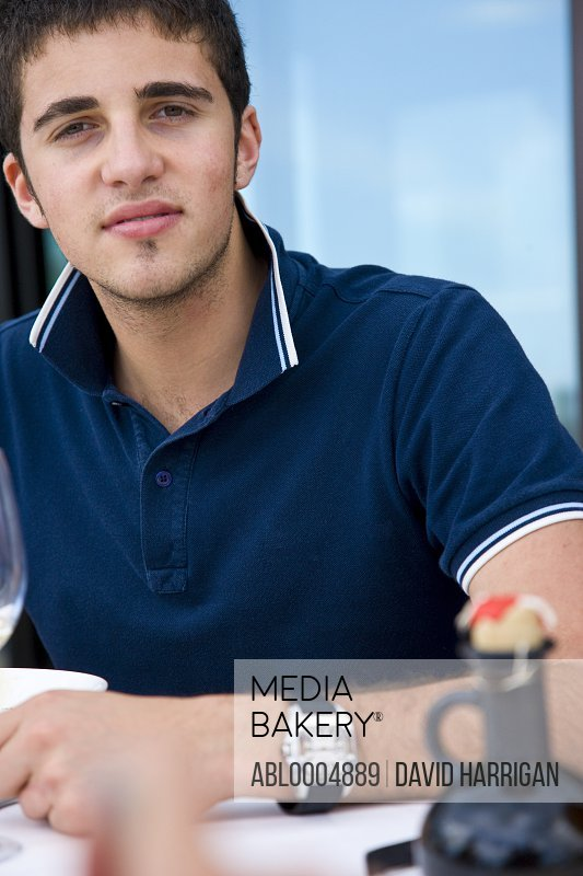 Close up of a young man sitting at restaurant table