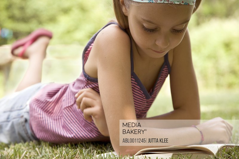 Girl lying on stomach reading book