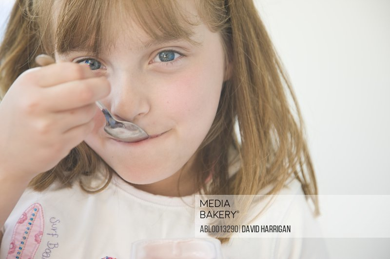 Young Girl Eating with Dessert Spoon