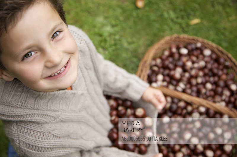 Smiling young boy holding chestnuts