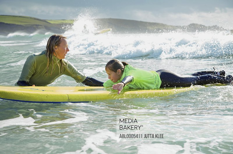 Woman in the sea holding a surfboard with a girl lying on it