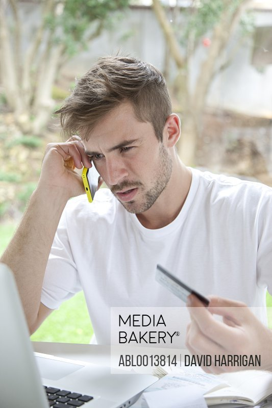 Man Using Smartphone Holding Credit Card