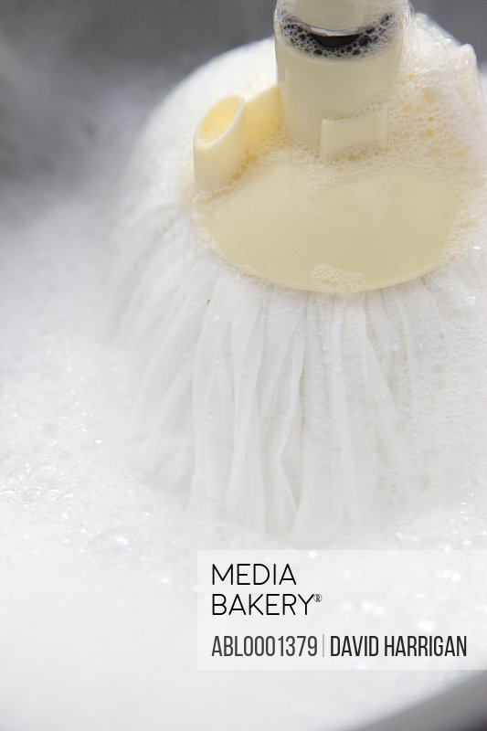 Close up of a floor mop plunging into soapy water