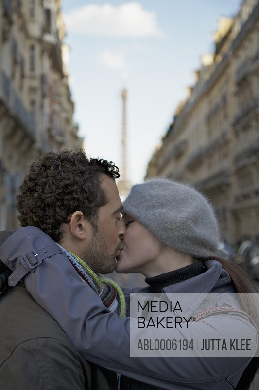 Close up of a couple kissing in a city street