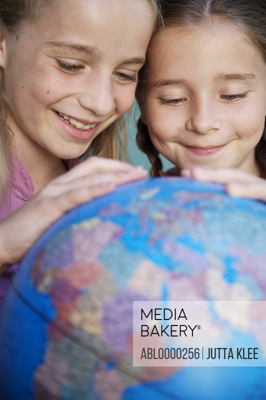 Two young girls touching and spinning  a world globe