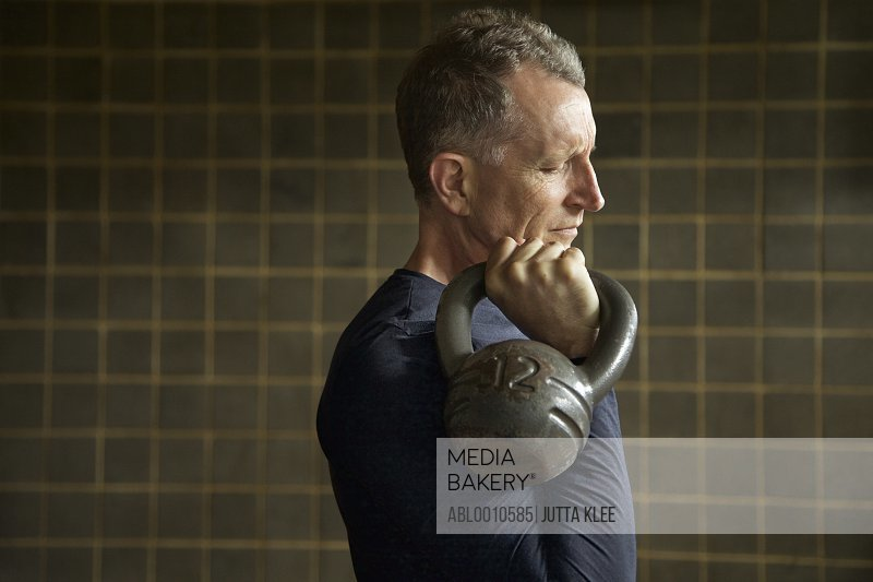 Profile of Mature Man Lifting Kettlebell