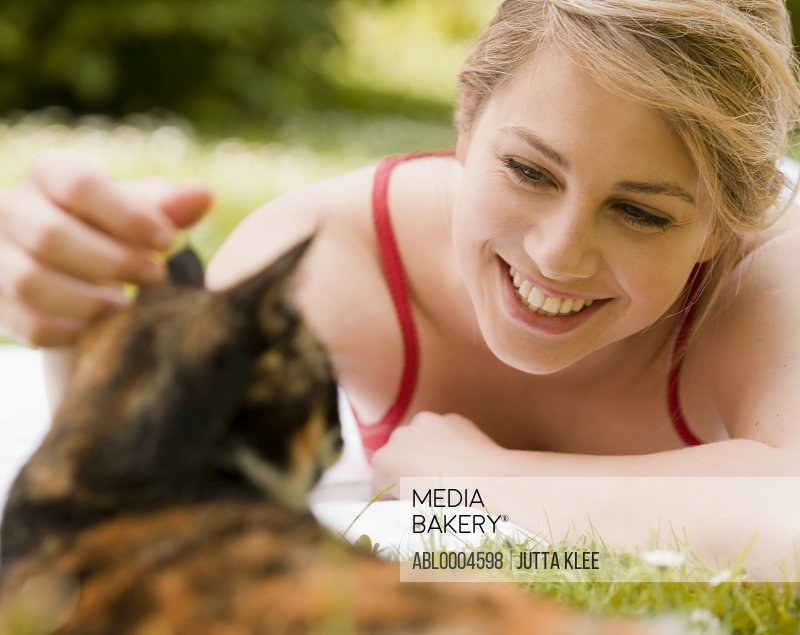 Young woman lying on the grass caressing a cat