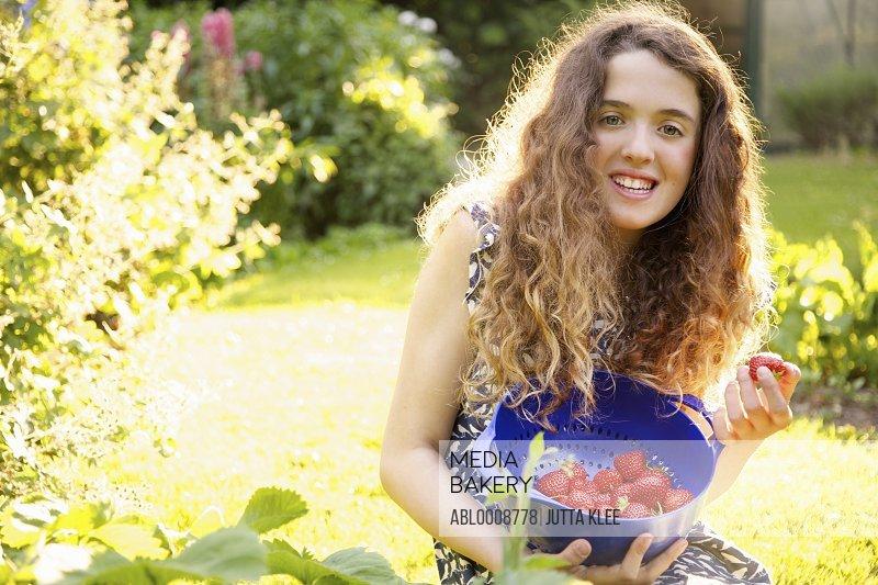 Smiling Teenage Girl Picking Strawberries in Garden