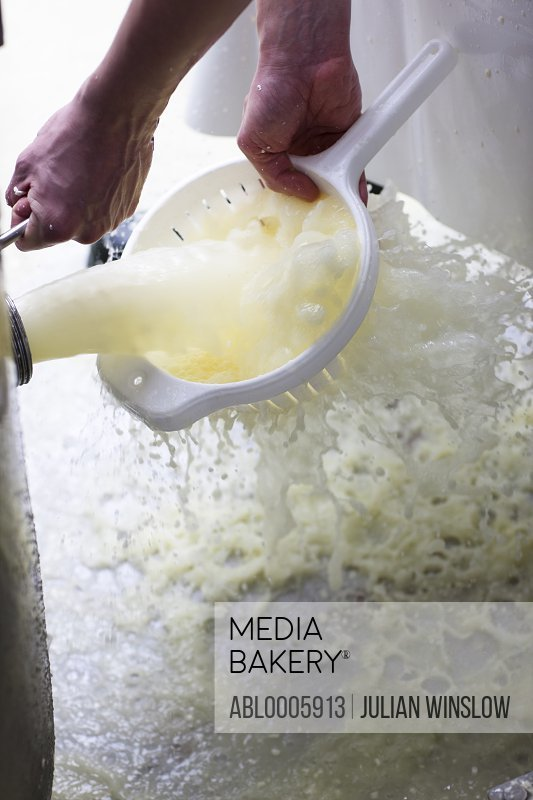 Close up of a man's hand washing cheese