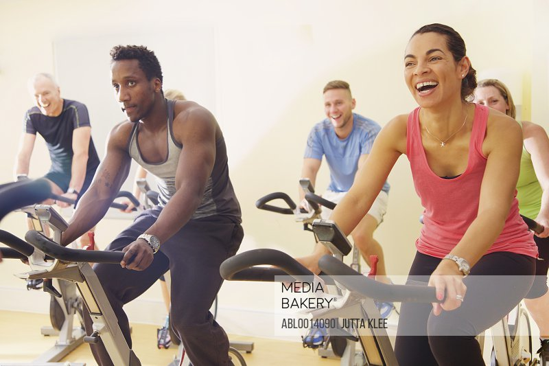 Group of People Using Exercise Bicycles at Fitness Class<br><span style='color: red'>May not be used for any Calendar use within all industries in North America thru December 31, 2018.</span><br>