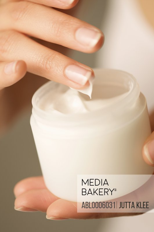 Close up of a woman's hands holding an open jar of cosmetic cream