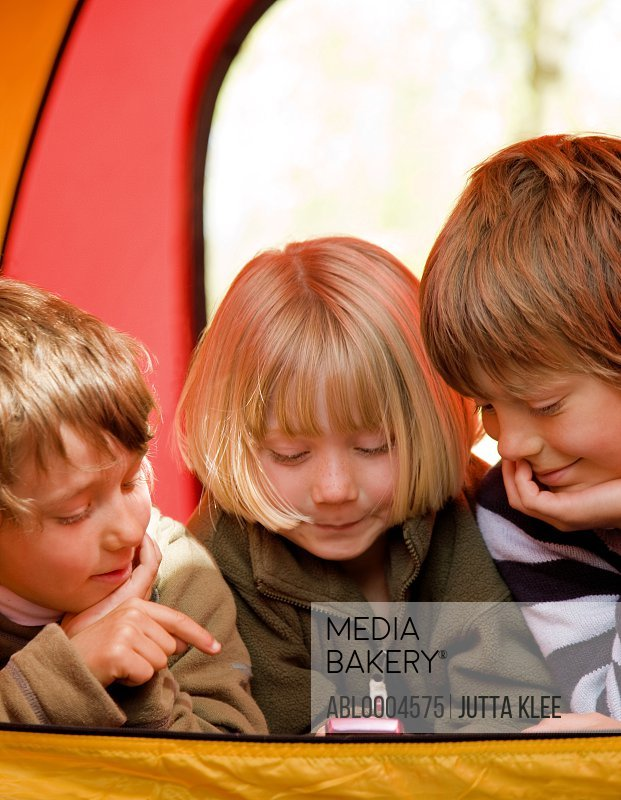 Portrait of three children lying in a tent text messaging on a cell phone