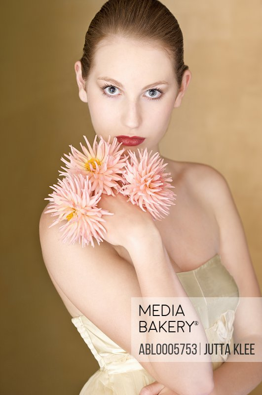 Young woman holding pink dahlias