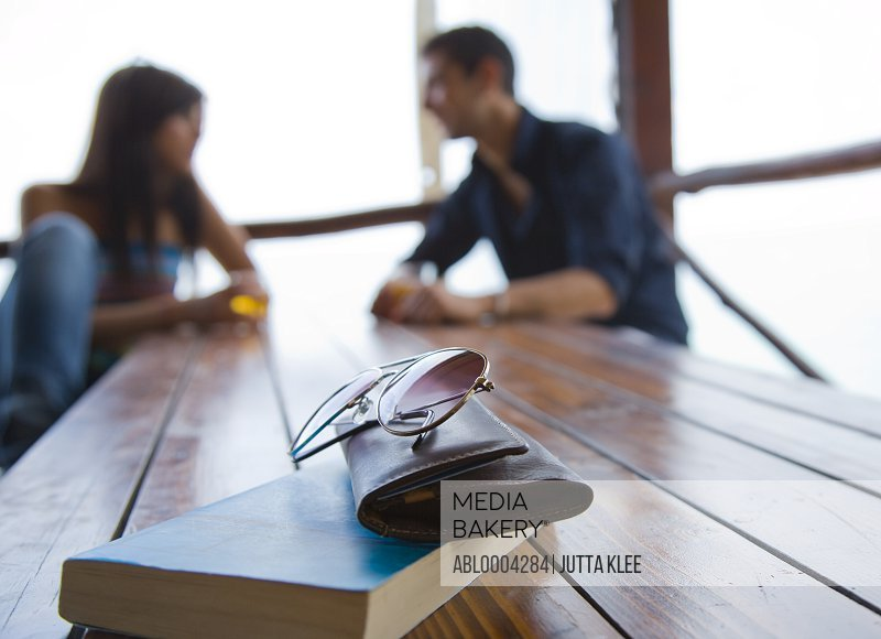 Close up of personal belongings on table with couple sitting