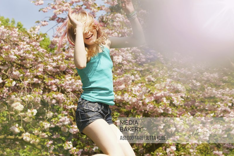 Teenage Girl Bouncing on Trampoline in front of Blooming Tree