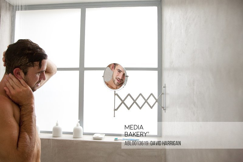 Man under Shower Looking in Mirror