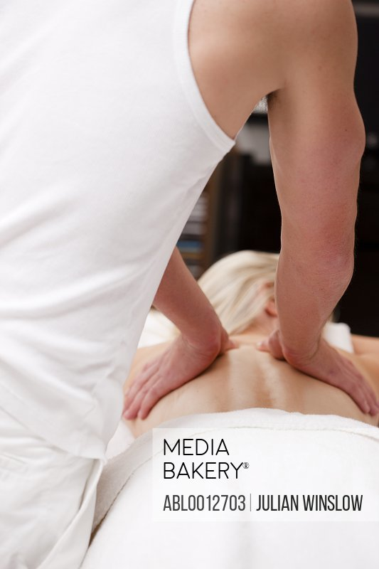 Back view of masseur giving a woman a back massage