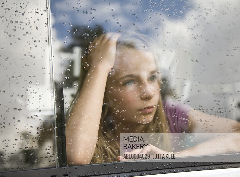 Portrait of a girl looking out of a car window