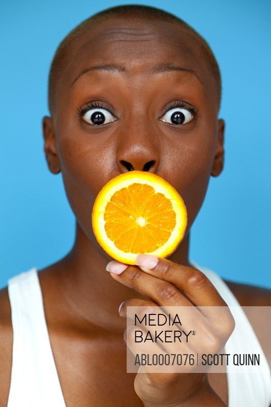 Young Woman Holding Orange Slice over Mouth