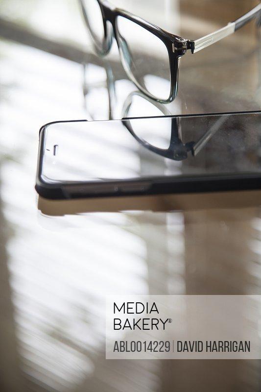 Eyeglasses and Smart Phone on Desk