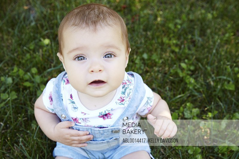 Close up of Baby Girl Sitting on Grass
