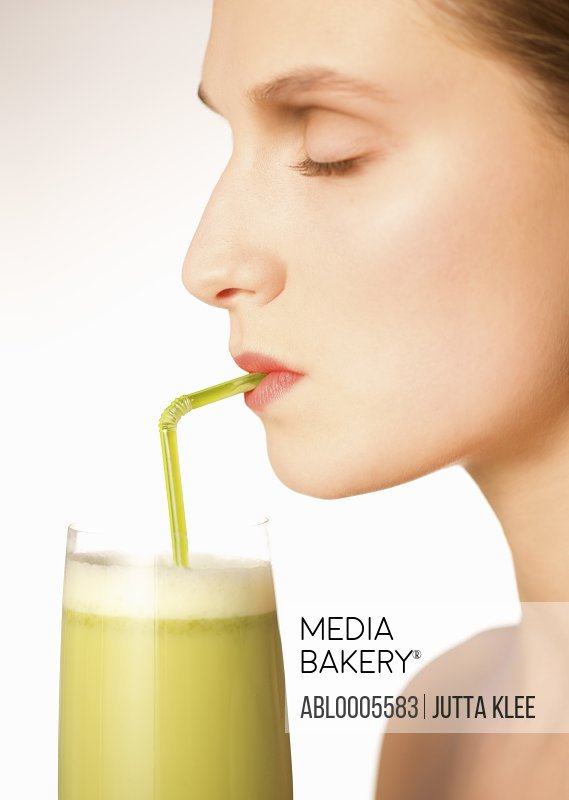 Profile of a woman with eyes closed drinking a vegetable smoothie with a straw