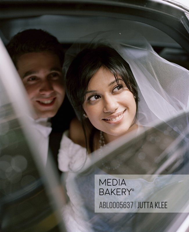 Bride and groom sitting inside a car