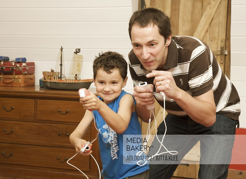 Man and young boy playing in the living room holding video game remote controls