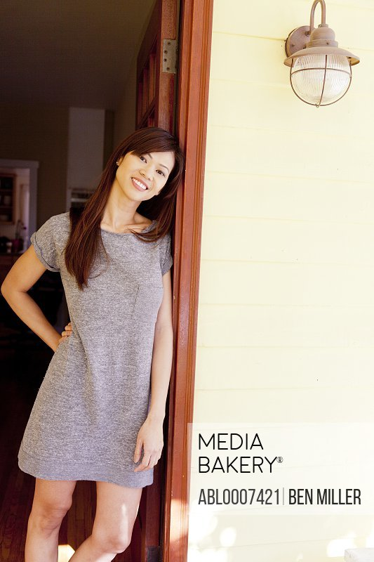 Smiling Woman Leaning against Doorframe Outside House