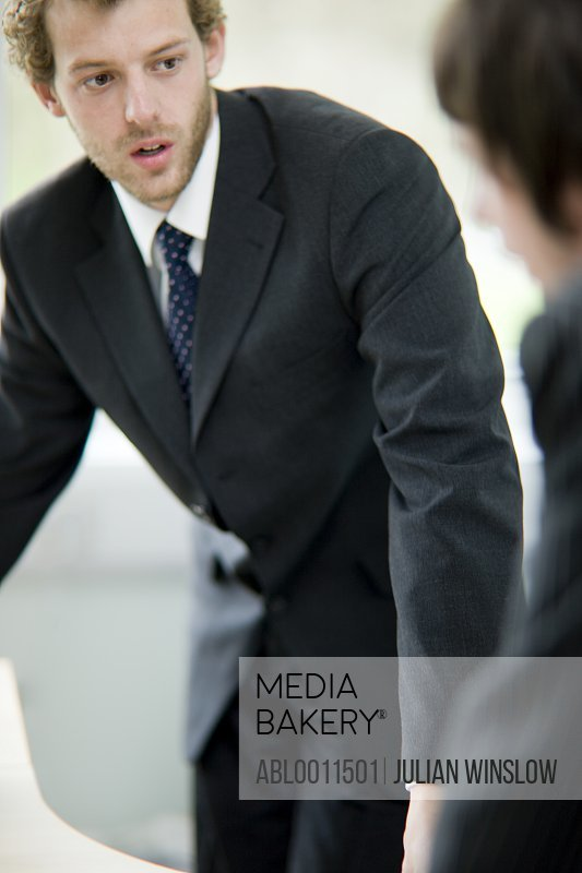 Portrait of a young businessman talking to colleague
