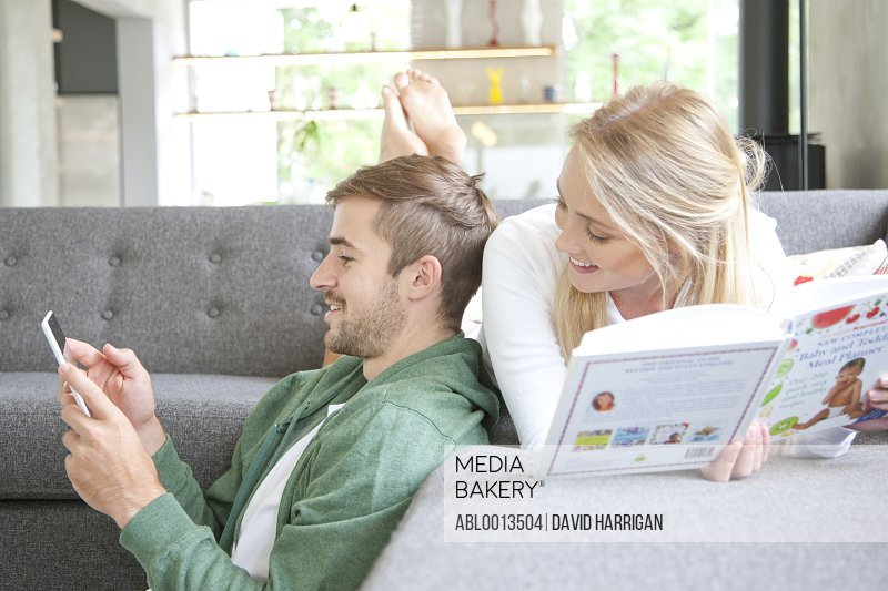 Man Using Smartphone  and Woman Reading Book on Sofa