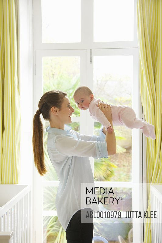 Mother Lifting Baby in Nursery