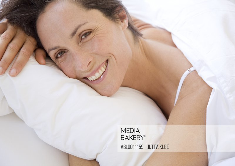 Smiling woman lying in bed hugging pillow