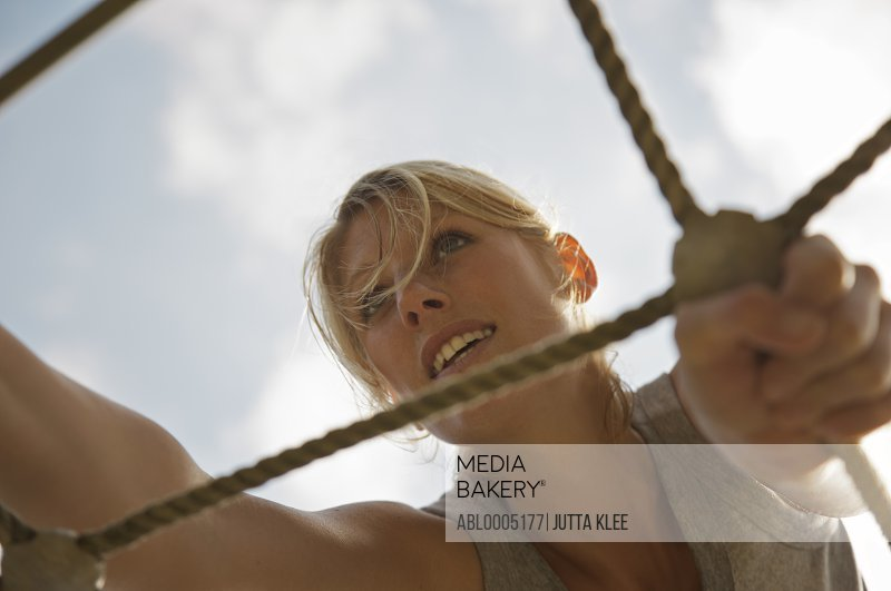 Young woman at obstacle course climbing a cargo net