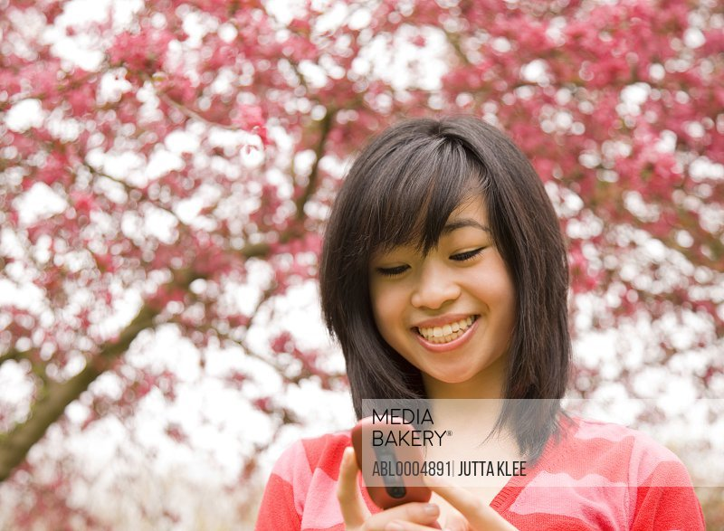Smiling young teenaged girl holding and looking at cell phone