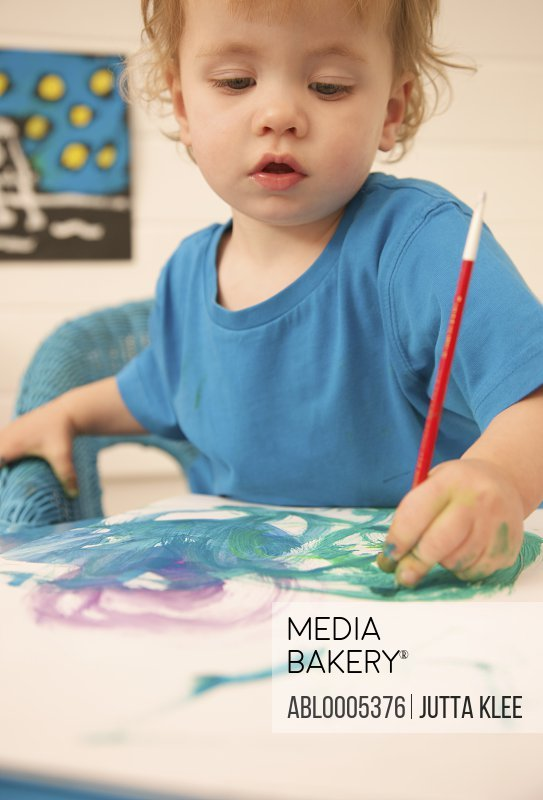 Young boy painting with watercolors