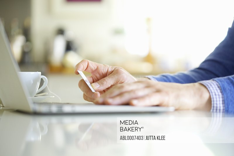 Close up of Man's Hands Holding Credit Card and Using Laptop