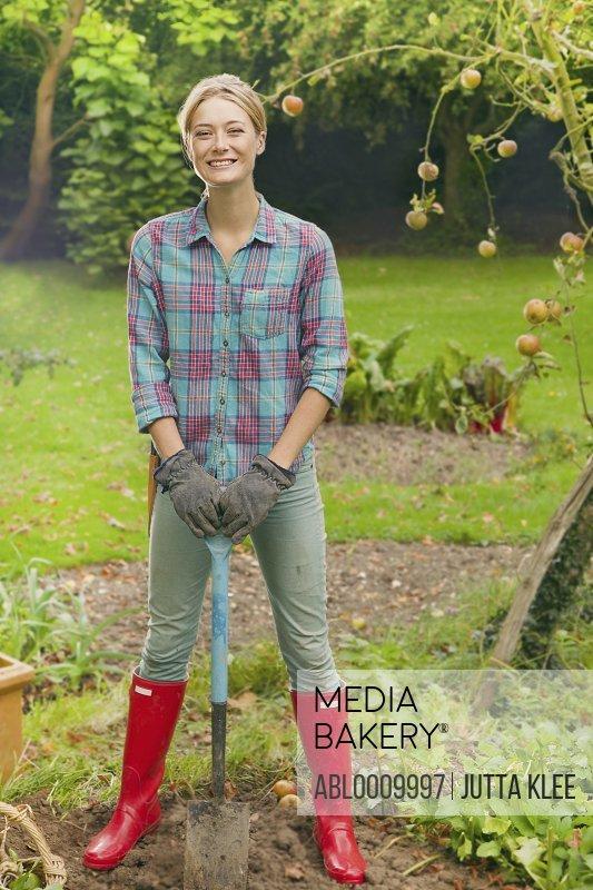 Woman In Garden Holding Spade