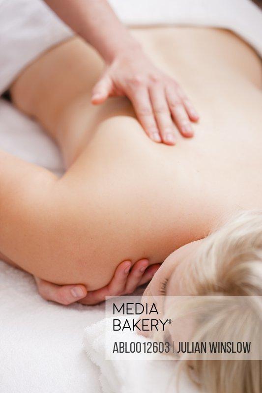 Masseur hands giving a woman a shoulder massage